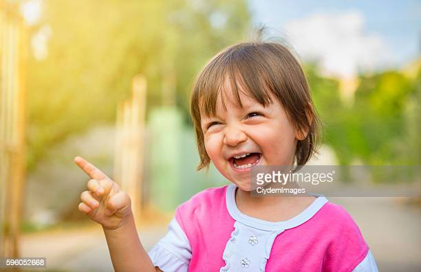 Portrait of laughing baby girl pointing somewhere with content s