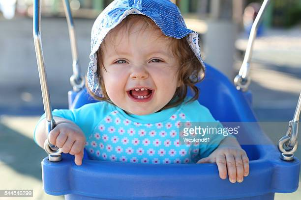 Portrait of laughing baby girl sitting on blue baby swing