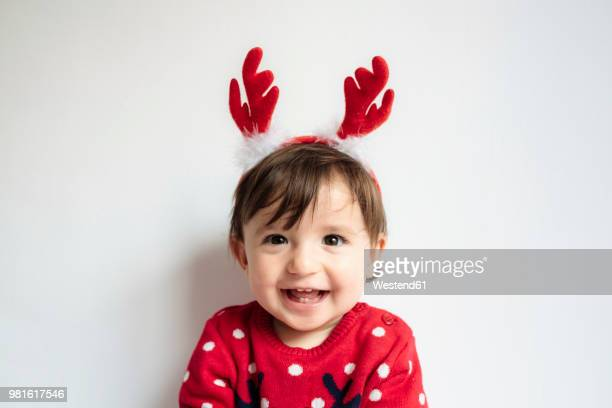 portrait of laughing baby girl wearing reindeer antlers headband - reindeer stock photos and pictures