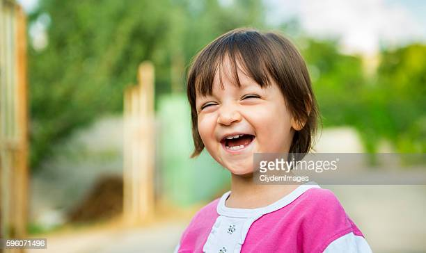 Portrait of laughing baby girl with content smile