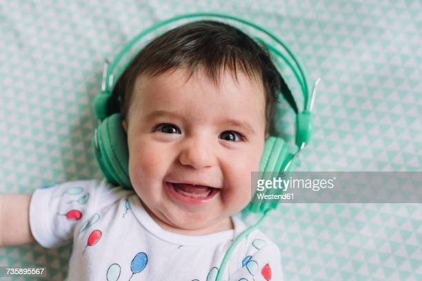 Portrait of laughing baby girl with headphones