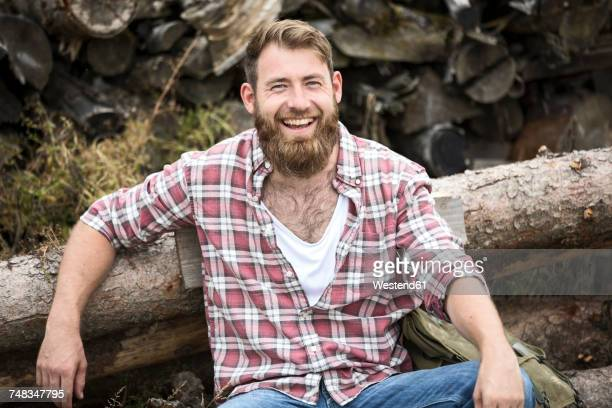 Portrait of laughing bearded man sitting on stack of wood
