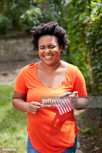 Portrait of laughing Black woman holding little American flag
