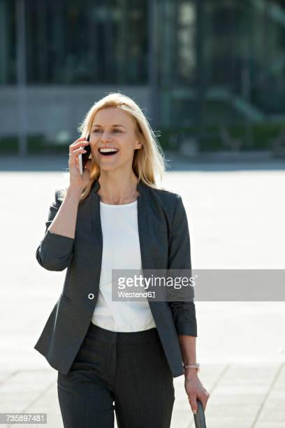 Portrait of laughing blond businesswoman on the phone