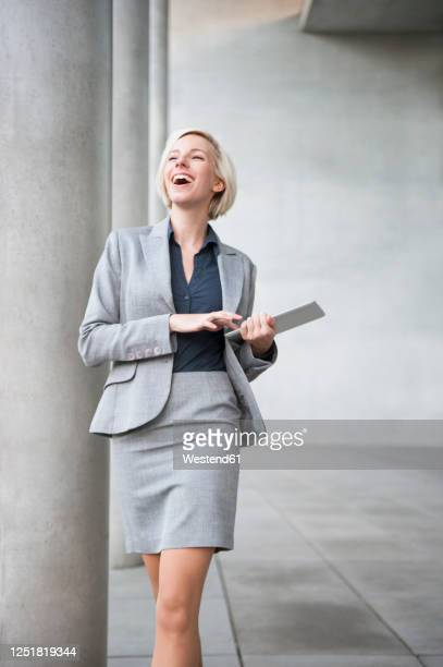 portrait of laughing blond businesswoman with tablet - businesswear stock-fotos und bilder