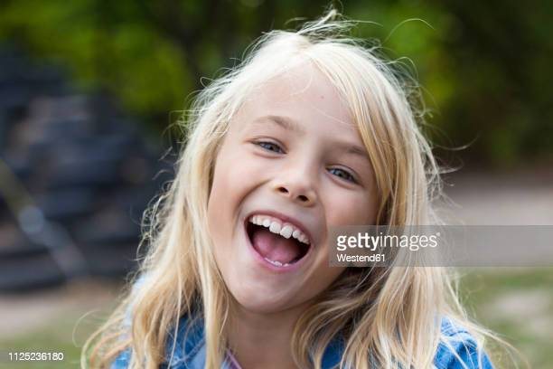 portrait of laughing blond girl outdoors - alleen één meisje stockfoto's en -beelden