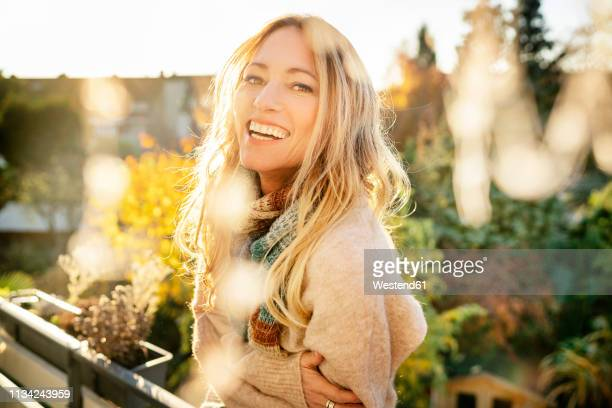 portrait of laughing blond mature woman on balcony at autumn - nur erwachsene stock-fotos und bilder