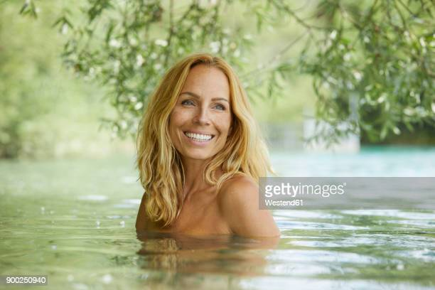 portrait of laughing blond woman bathing in lake - mujer desnuda naturaleza fotografías e imágenes de stock