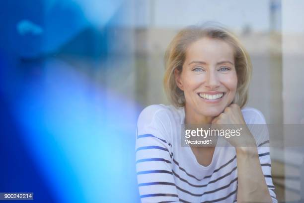 Portrait of laughing blond woman behind window pane
