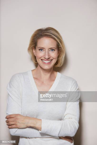 Portrait of laughing blond woman in front of light background