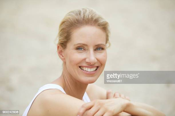 portrait of laughing blond woman on the beach - schönheit stock-fotos und bilder