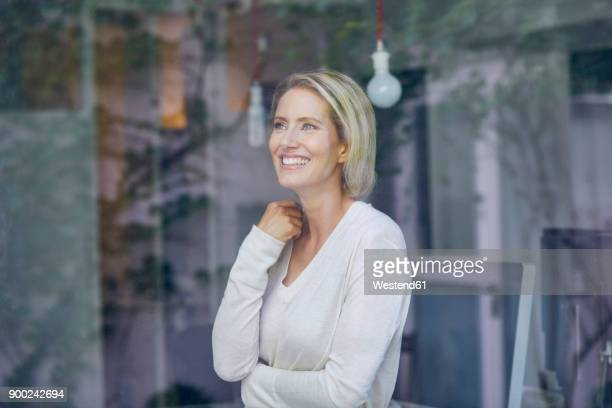 Portrait of laughing blond woman standing behind window pane