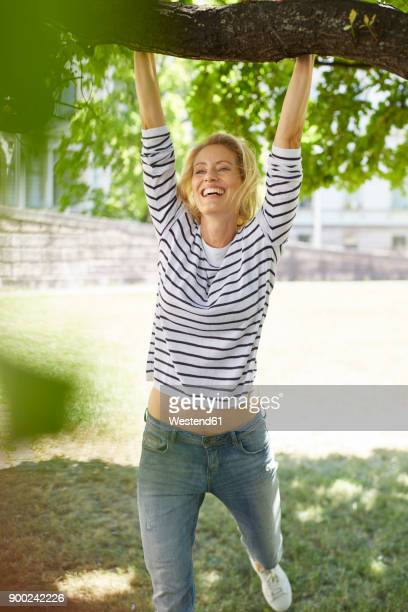 portrait of laughing blond woman swinging at branch of a tree - sorglos stock-fotos und bilder