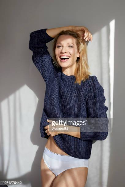 portrait of laughing blond woman wearing knit pullover and panties leaning against wall - dessous stock-fotos und bilder