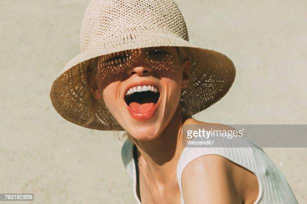 portrait of laughing blond woman wearing summer hat - sommer stock-fotos und bilder