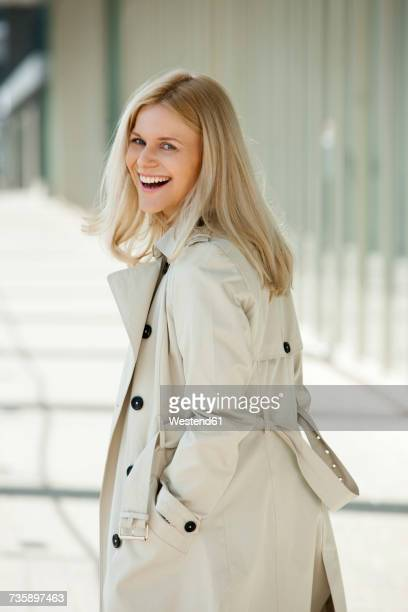Portrait of laughing blond woman wearing trench coat