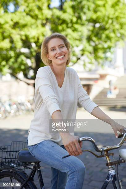 Portrait of laughing blond woman with bicycle