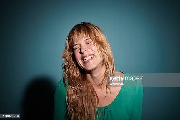 Portrait of laughing blond woman with closed eyes in front of blue background