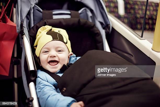 Portrait of laughing boy in pram