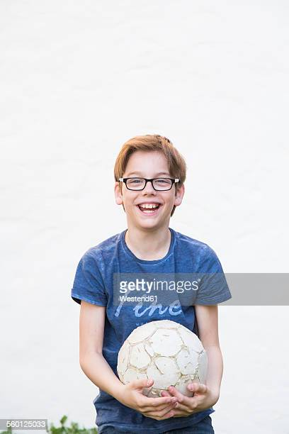 Portrait of laughing boy with soccer ball