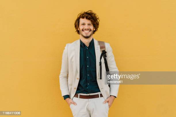 portrait of laughing businessman with backpack standing in front of yellow wall - mid adult men stock-fotos und bilder