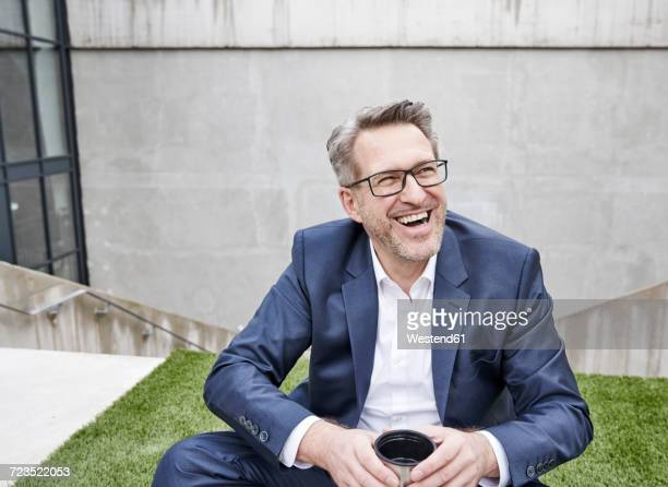 Portrait of laughing businessman with cup of coffee