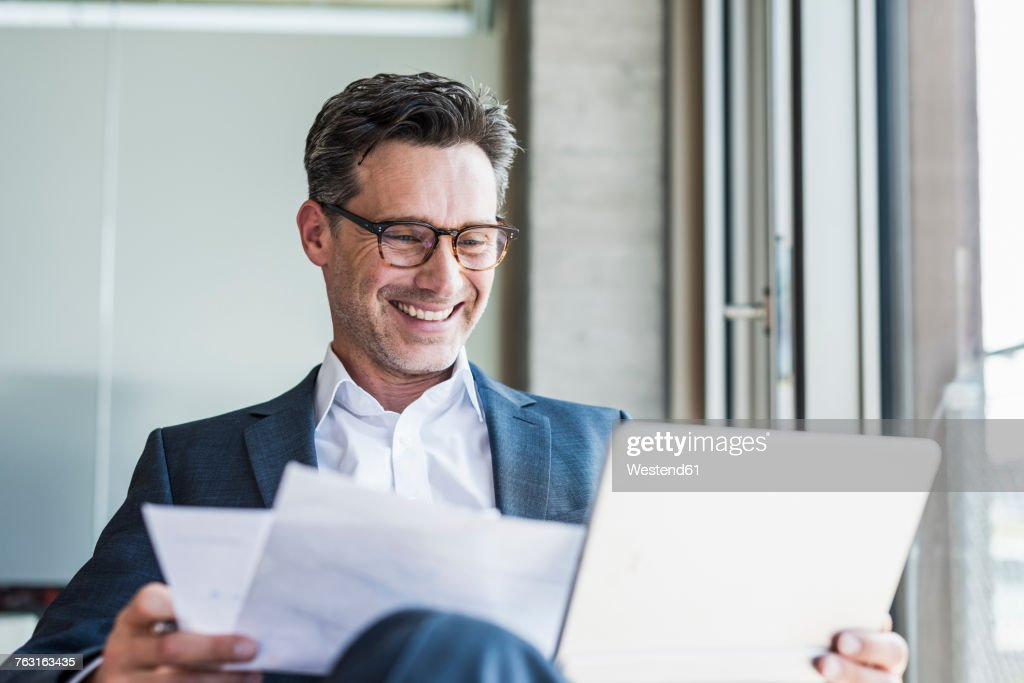 Portrait of laughing businessman with documents looking at tablet : Stock-Foto