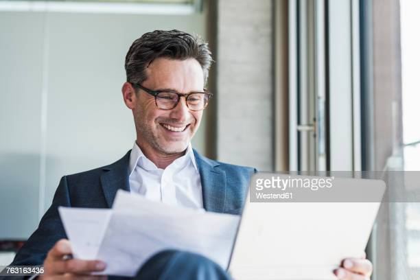portrait of laughing businessman with documents looking at tablet - näringsliv och industri bildbanksfoton och bilder