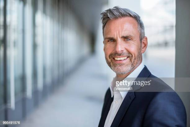 Portrait of laughing businessman with grey hair and beard