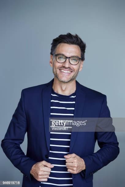 portrait of laughing businessman with stubble wearing blue suit coat and glasses - gray coat stock pictures, royalty-free photos & images
