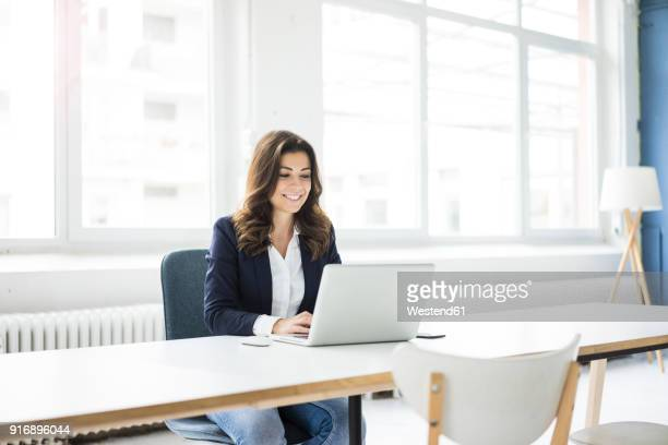 portrait of laughing businesswoman sitting at desk in the office working on laptop - using laptop stock pictures, royalty-free photos & images