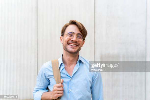 portrait of laughing casual businessman - hellblau stock-fotos und bilder