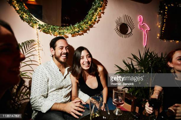 Portrait of laughing couple on date in night club