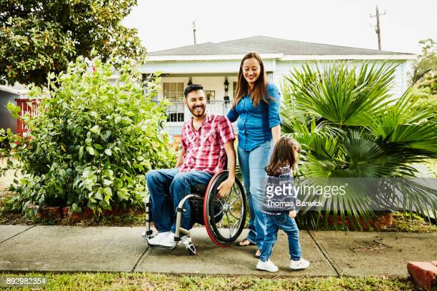 Portrait of laughing family in front of home with daughter walking away