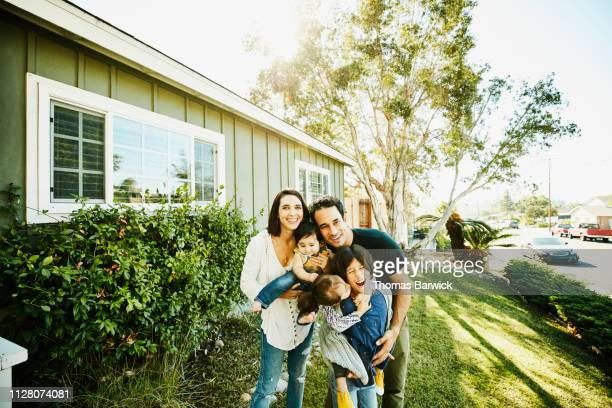 Portrait of laughing family standing in front yard of home