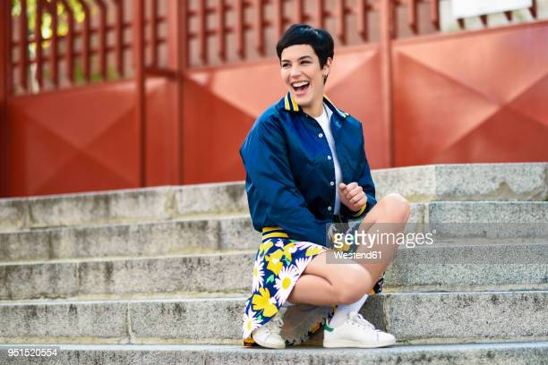 Portrait of laughing fashionable young woman crouching on stairs
