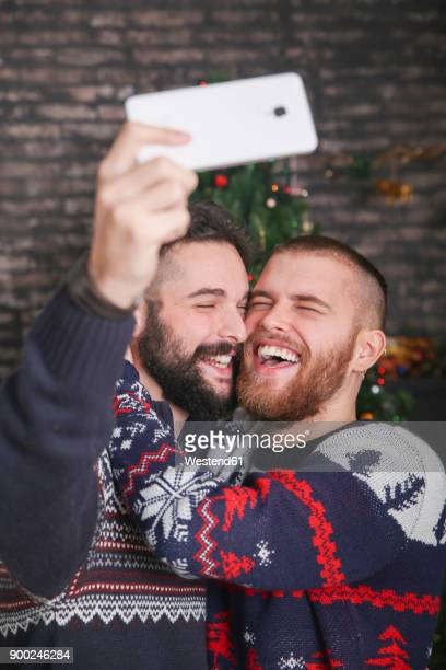 Portrait of laughing gay couple taking selfie with smartphone at Christmas time at home