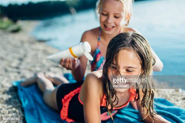 portrait of laughing girl on the beach with her friend - little girl laying on the beach stock photos and pictures
