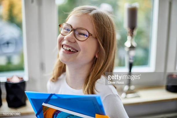 portrait of laughing girl with folder at home - linda oliver fotografías e imágenes de stock