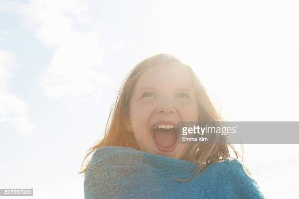 portrait of laughing girl wrapped in towel at sunlit coast - camber sands stock photos and pictures