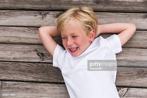portrait of laughing little boy lying on a jetty - nur jungen stock-fotos und bilder
