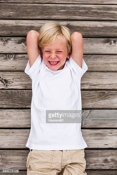 Portrait of laughing little boy lying on a jetty