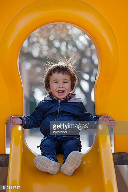 Portrait of laughing little boy sitting on a yellow shute
