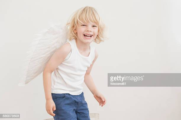 portrait of laughing little boy with angle wings - male angel stock photos and pictures