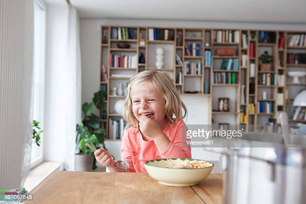 Portrait of laughing little girl eating spaghetti