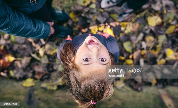 Portrait of laughing little girl standing in the woods, top view