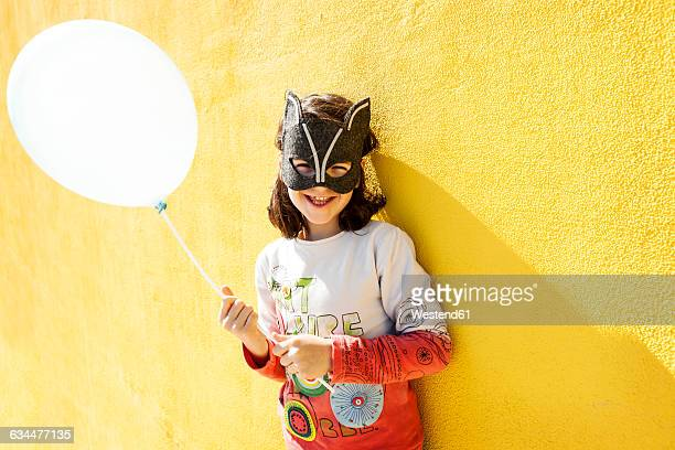 Portrait of laughing little girl with balloon wearing animal mask in front of yellow wall