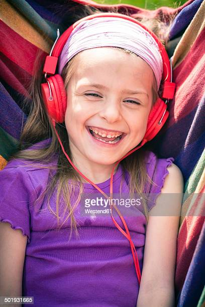 Portrait of laughing little girl with red headphones