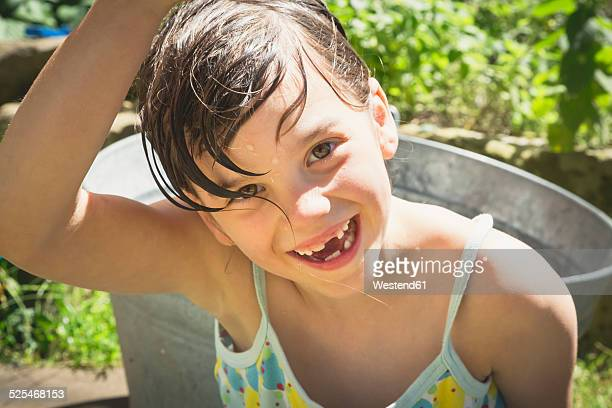 Portrait of laughing little girl with wet hair in the garden