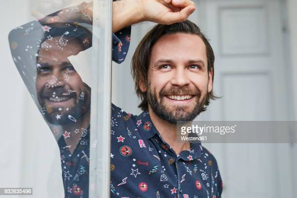 portrait of laughing man at open window - mid adult men stock pictures, royalty-free photos & images